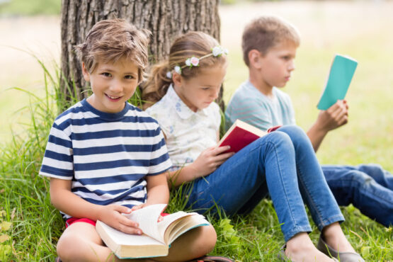 Kids sitting under tree and reading books in park on a sunny day