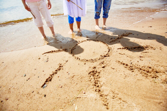 Legs of three girls standing on sand with picture of sun